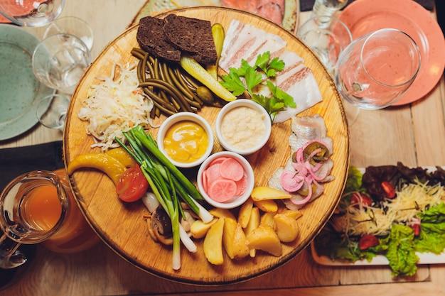 Italienische antipasti-weinsnacks eingestellt. brushettas, käsesorten, mediterrane oliven, gurken, parmaschinken mit melone, salami und wein in gläsern