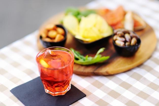 Italienische aperitifs / aperitifs: ein glas cocktail (sekt mit aperol) und eine vorspeisenplatte auf dem tisch