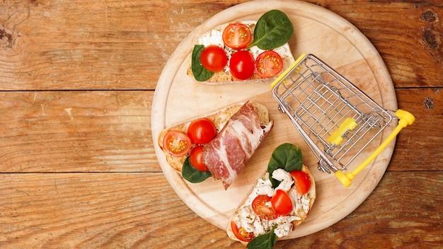 Italienische bruschetta auf einem hölzernen brettgeschäftkorb-zutateneinkauf