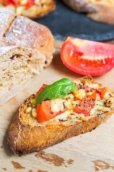 Italienische bruschetta mit gebratenen tomaten, mozzarella-käse und