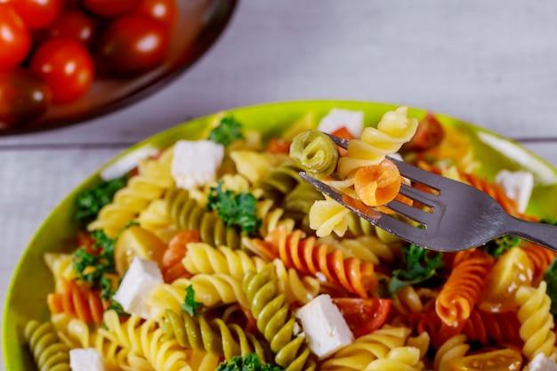 Italienische bunte nudelrotini mit kirschtomaten auf weißem hölzernem hintergrund.