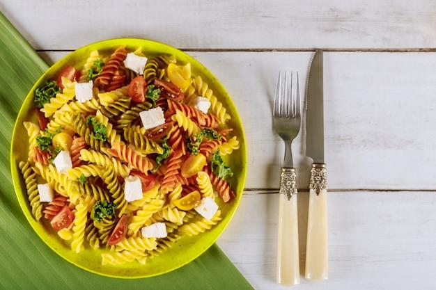 Italienische bunte nudelrotini mit kirschtomaten auf weißer holzoberfläche