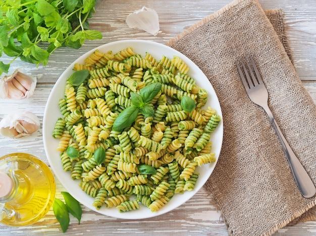 Italienische calssic pasta mit grünem pesto auf einem weißen teller auf einem rustikalen holztisch