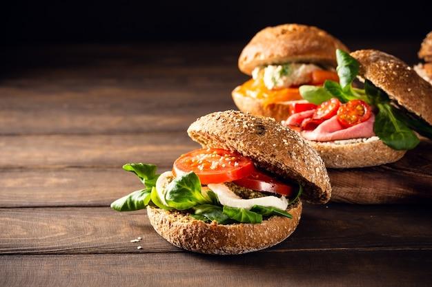 Italienische caprese-sandwiches mit frischen tomaten, mozzarella und feldsalat, mehrkornbrötchen. gesundes lebensmittelkonzept mit kopienraum
