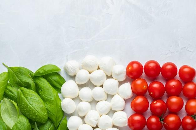 Italienische flagge mit tomaten-mozzarella und basilikum.