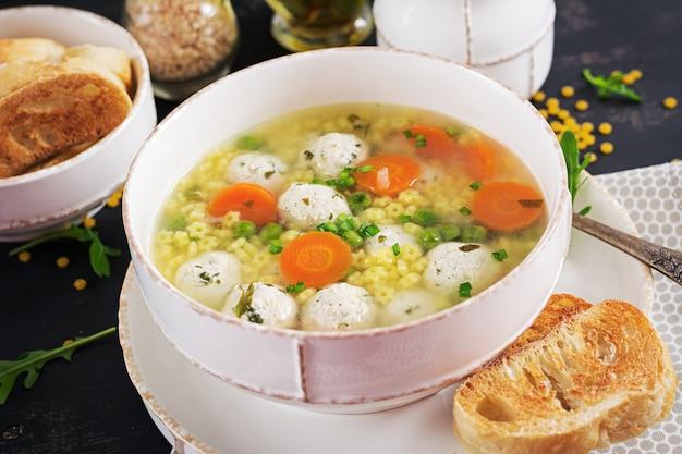 Italienische fleischklöschensuppe und stelline teigwaren in der schüssel auf schwarzer tabelle. diätetische suppe. baby-menü. leckeres essen.