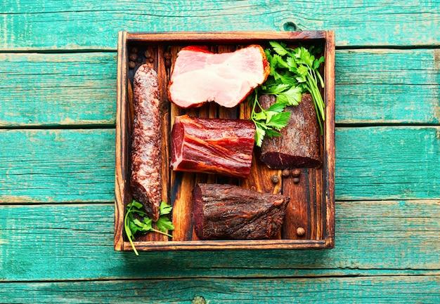 Italienische fleischplatte. gepökeltes fleisch und würste auf holzuntergrund