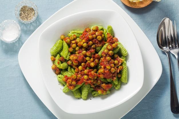 Italienische frische traditionelle sardische nudelgnocchi mit spinat und erbsen-tomatensauce.