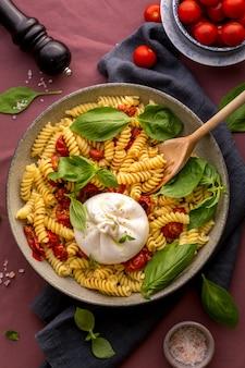 Italienische fusillinudeln mit burattakäse, kirschtomaten und frischem basilikum