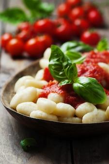 Italienische gnocchi mit tomaten und basilikum