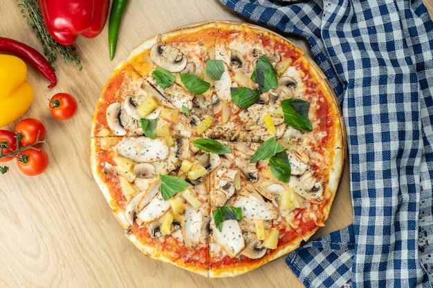 Italienische, hausgemachte hawaiianische pizza mit huhn und ananas auf einem holztisch.