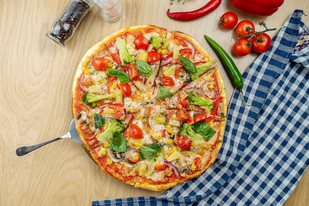 Italienische, hausgemachte italienische, hausgemachte vegetarische pizza mit pilzen, zwiebeln und brokkoli auf einem holztisch auf einem holztisch.