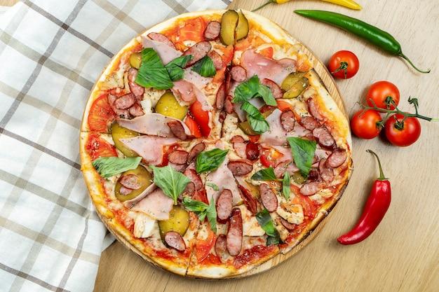 Italienische, hausgemachte pizza mit fleisch, speck, salami und paprika auf einem holztisch.