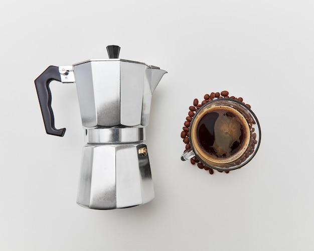 Italienische kaffeemaschine und die tasse frisch duftendes kaffeegetränk auf weißem hintergrund mit kopienraum. flach legen