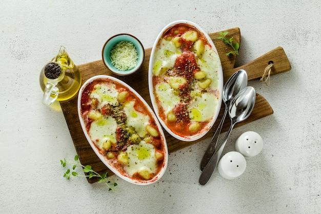 Italienische kartoffelknödel gnocchi alla sorrentina mit mozzarella, im ofen mit tomatensauce und kräutern gebacken.