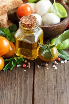 Italienische kochzutaten mozzarella, tomaten, basilikum, olivenöl und andere auf holz schließen mit kopienraum