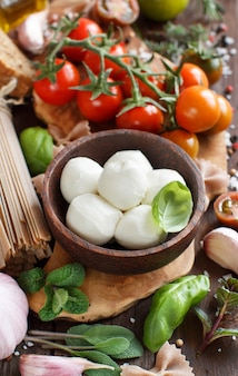 Italienische kochzutaten: mozzarella, tomaten, basilikum, olivenöl und andere