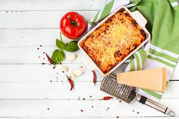 Italienische küche-lasagne. produkte für lasagne-tomaten, basilikum, teig, auflaufform.