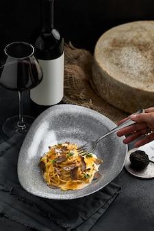 Italienische küche - spaghetti mit schwarzem trüffel auf einem grauen teller und einer flasche wein. selektiver fokus. vertikal.