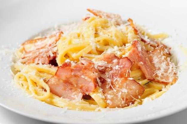 Italienische küche tagliatelli carbanara auf rustikalem küchentischhintergrund der platte