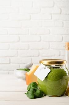 Italienische küche. zubereitung hausgemachter italienischer pesto-sauce. hausgemachte pesto-sauce in einem glas mit leerem etikett, mock-up-design