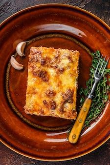 Italienische lasagne mit tomaten-bolognese-sauce und hackfleisch auf einem rustikalen teller