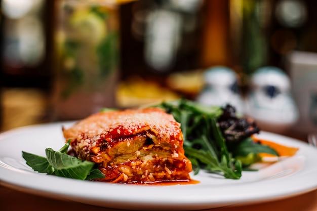 Italienische lasagne serviert mit rucolasalat
