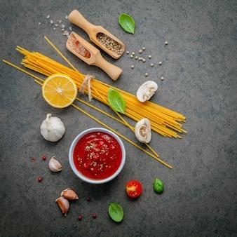 Italienische lebensmittel- und menükonzeptspaghettis mit bestandteilen auf dunkler tabelle.