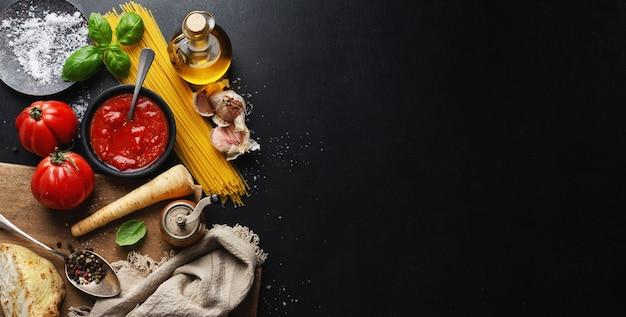 Italienische lebensmitteloberfläche mit spaghetti-gemüse und tomatensauce auf dunkler oberfläche