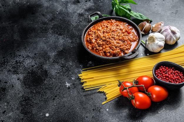 Italienische lebensmittelzutaten für spaghetti bolognese. rohe nudeln, basilikum, rinderhackfleisch, tomaten. schwarzer hintergrund