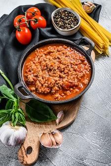 Italienische lebensmittelzutaten für spaghetti bolognese. rohe nudeln, basilikum, rinderhackfleisch, tomaten