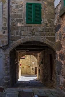 Italienische mittelalterliche dorfdetails, historischer steinbogen, altes tor, alte stadtsteingebäudearchitektur santa fiora, toskana, italien.