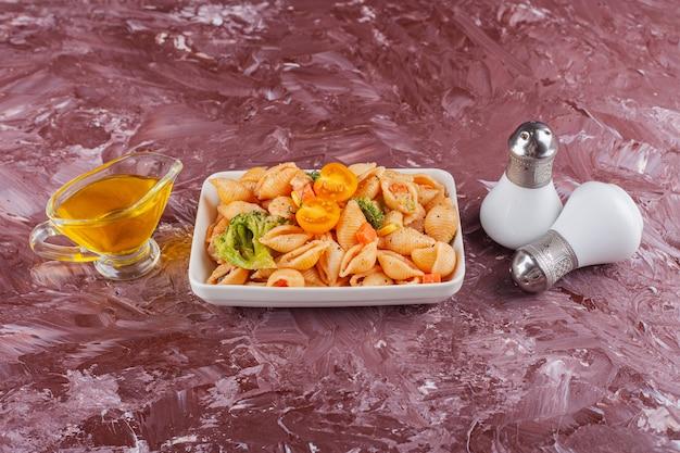 Italienische muschelnudeln mit öl und gemischtem gemüse auf leichtem tisch.
