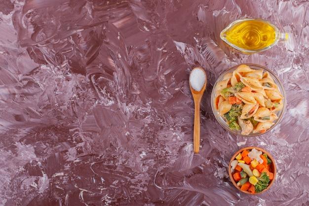 Italienische muschelnudeln mit öl und gemischtem gemüsesalat auf hellem tisch.