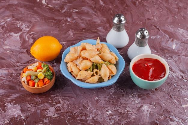Italienische muschelnudeln mit tomatensauce und gemischtem gemüsesalat auf hellem tisch.