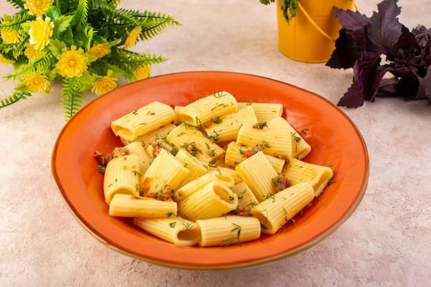 Italienische nudeln mit vorderansicht, lecker gekocht mit getrocknetem grün und gesalzenem runden orangefarbenen teller mit blume auf rosa schreibtisch