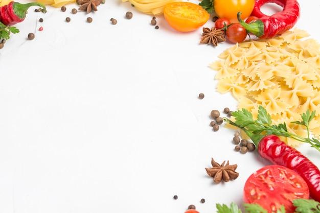Italienische nudeln verschiedener arten mit gewürzen, paprika, eiern, gelben und roten tomaten auf einem weißen steinhintergrund. konzept, das italienische nudeln und soße kocht