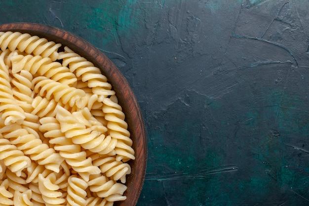 Italienische nudeln von oben aus der nähe, die köstlich in braunem topf auf dunkelblauem schreibtisch schauen