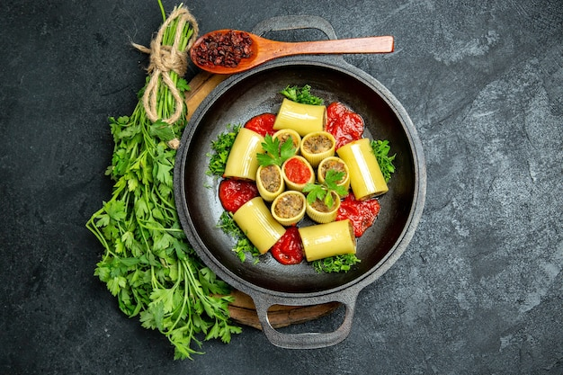 Italienische nudeln von oben mit grüner tomatensauce und fleisch in der pfanne auf grauem raum