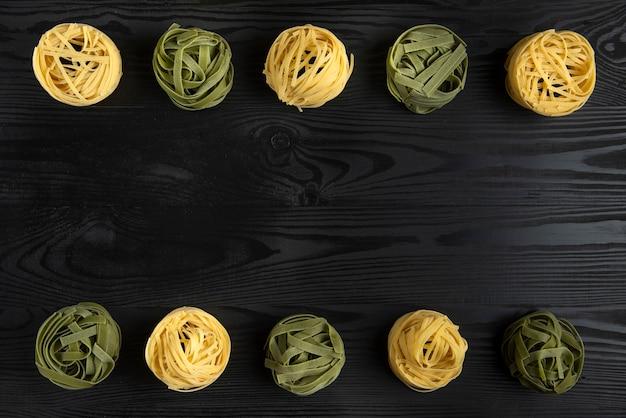 Italienische nudelsorten auf dem schwarzen tisch