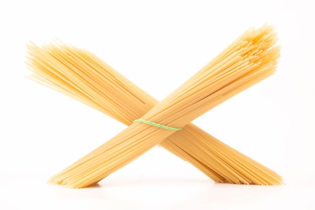 Italienische nudelspaghetti auf einem weißen hintergrund. mehlprodukte und lebensmittel beim kochen