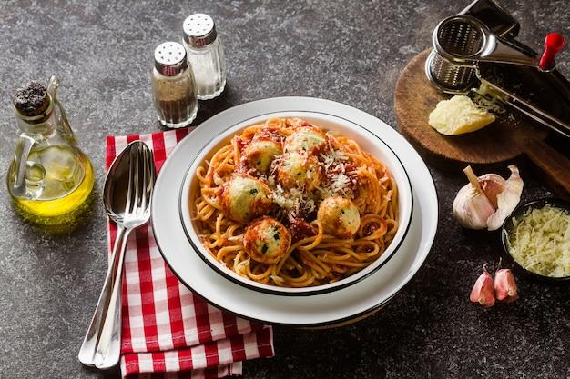Italienische nudelspaghetti mit ricotta-käsebällchen in tomatensauce auf dem tisch mit parmesan.