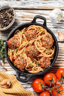 Italienische nudelspaghetti mit tomatensauce und fleischbällchen in gusseiserner pfanne mit parmesan. weißer hölzerner hintergrund. draufsicht