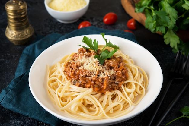 Italienische pasta bolognese mit grüns auf einem schwarzen hintergrund, nahaufnahme