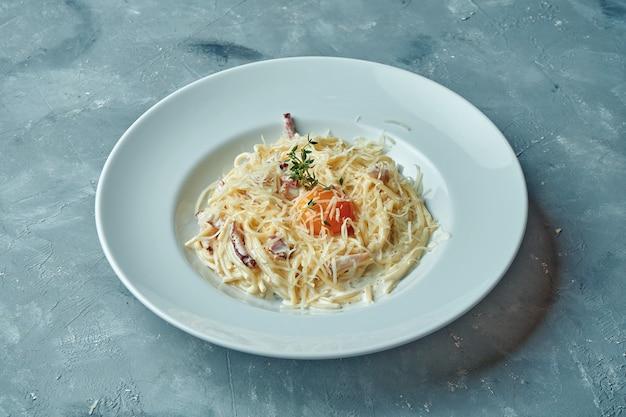 Italienische pasta carbonara mit speck, cremiger sauce und eigelb, käse in einem weißen teller auf grauer oberfläche
