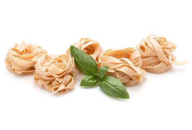 Italienische pasta fettuccine nest und basilikumblätter isoliert auf weißem hintergrund ausschnitt