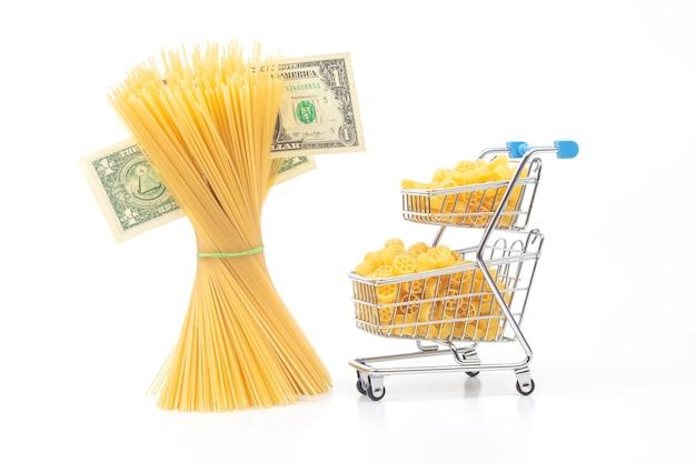 Italienische pasta in einem einkaufskorb vom markt mit einem dollarschein. mehlprodukte und lebensmittel beim kochen