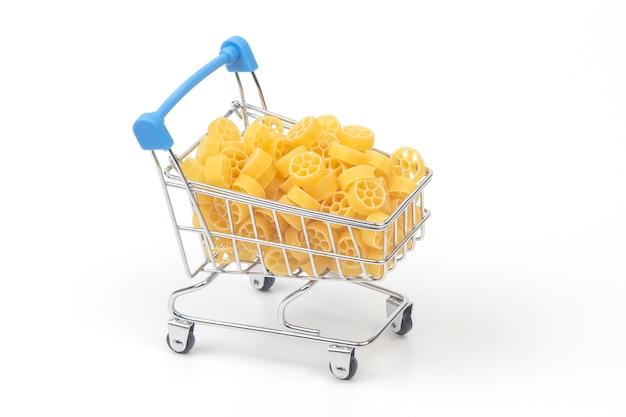 Italienische pasta in einem kleinen einkaufswagen auf weißem hintergrund.