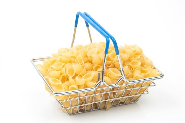 Italienische pasta in einem kleinen warenkorb auf weißem hintergrund.