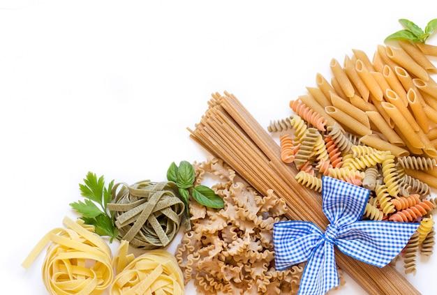 Italienische pasta mit basilikum und petersilie auf einem weißen hintergrund mit kopienraum